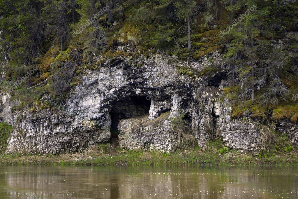 natural cave in the limestone cliff of the river bank
