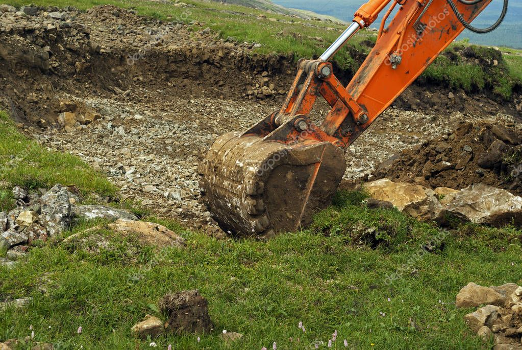 bucket of a working excavator tears off the grass and soil cover, digging a trench