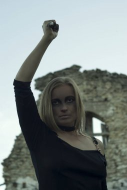 woman in a black dress with an ominous make-up swings a bone knife against a background of ruins in a gloomy atmosphere