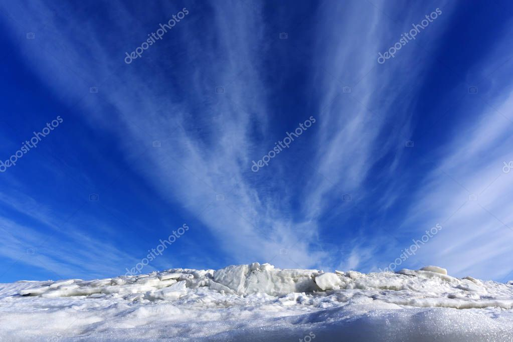 bright blue spring sky with cirrus clouds over melting ice and sno