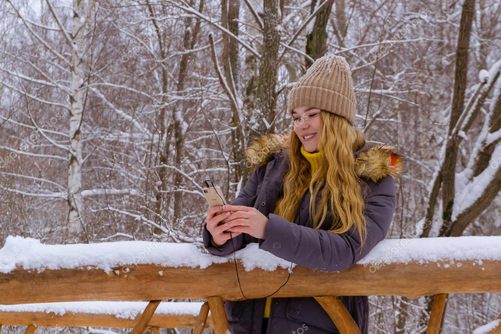 smiling girl in a winter park looks on her smartphone with a headset