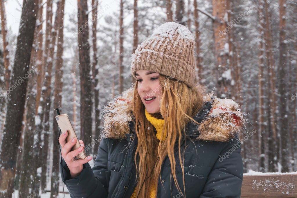 girl talking on the phone sitting on a bench in the winter park