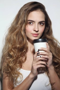 Young beautiful girl with long curly hair and cup of coffee in her hands