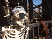 A close up of skeleton at the entrance of pirate themed playground for kids.