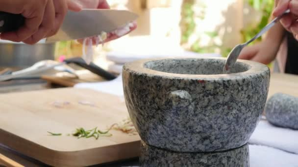 Pepper and another spices in stone mortar with pestle for thai chili sauce . Woman preparing sauce for thai soup tom yam. Close Up. 4k