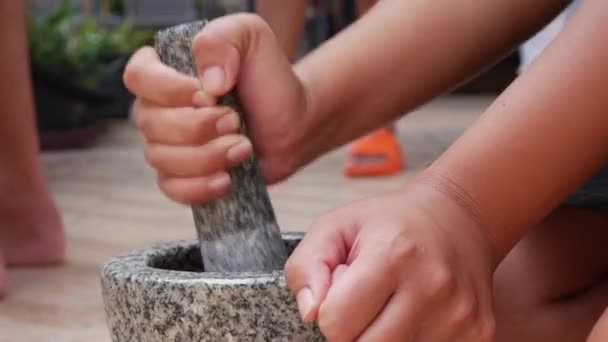 Thai chilli and garlic pounding in stone mortar with pestle. Woman preparing sauce for thai soup tom yam. Close Up. 4k