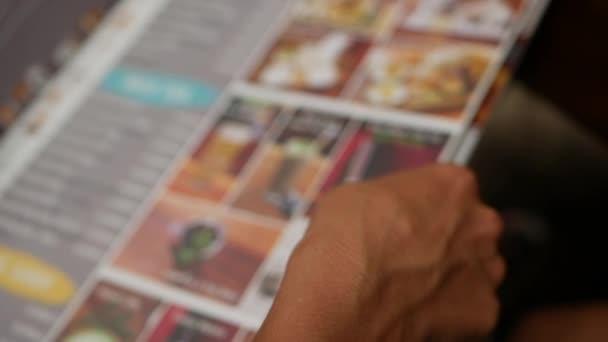 Nesoustředěný výprk výběru nápojů z menu v baru klouzání prstem přes papír