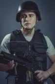 Photo paintball sport player wearing protective helmet aiming pistol ,black armor and machine gun