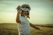 Fotografie Šťastný chlapec v západu slunce hraje že letec, nosí pilotní brýle letadel a nejaky karton jako křídla