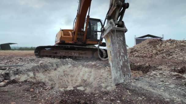 Excavator with hydraulic hammer drill at work breaking down earth for construction ground foundation