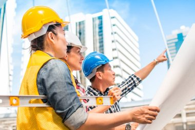 Three industrial engineer wear safety helmet engineering working and talking with drawings inspection on building outside. Engineering tools and construction concept.