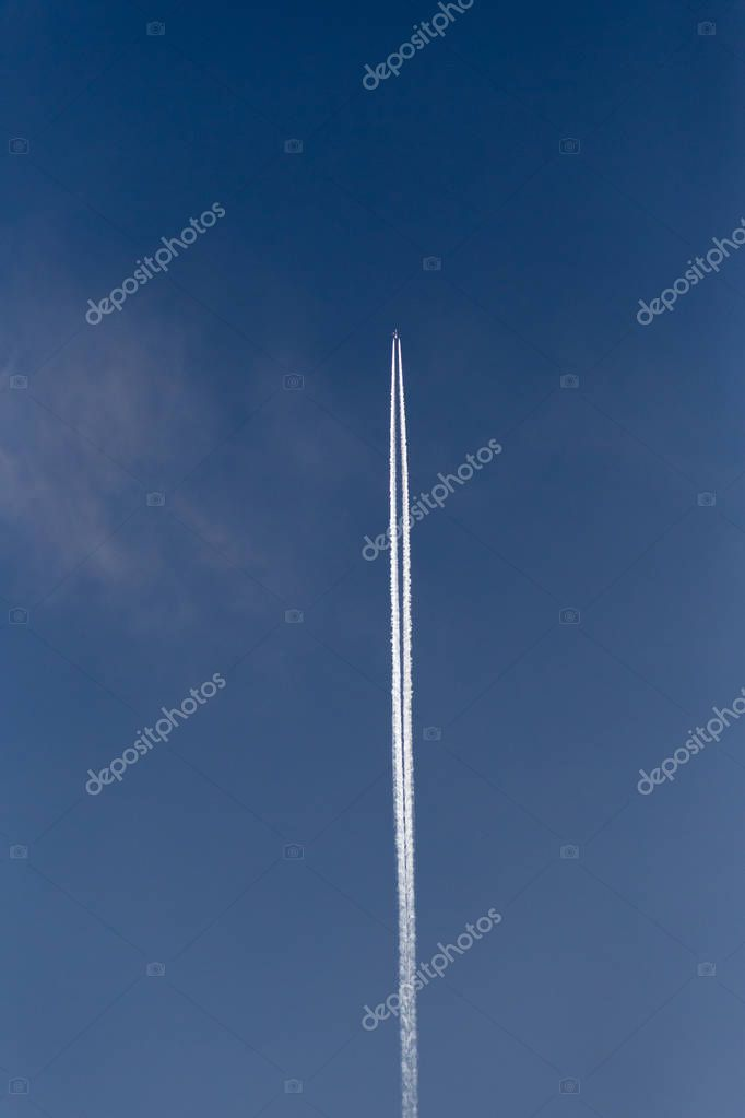 jet with contrails on blue sky high above on a spring sunny day in south germany