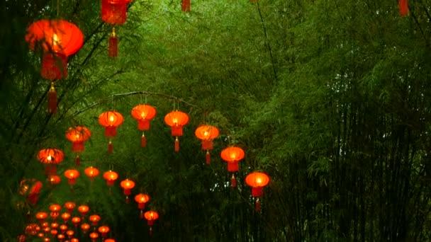 Řádky v tradičním čínském stylu červené lucerny visící na bambus strom tunnel arch.