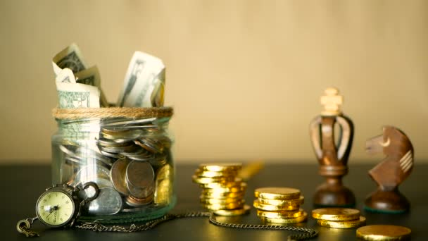 Saving money coin in jar. Symbol of investing, keeping money concept. Collecting cash banknotes in glass tin. American dollars with increasing columns of gold coins on black with retro clock, chess.
