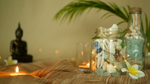 Glass bottle filled with seashells, corals, marine items with candle lights, plumeria flowers, sitting buddha for decor