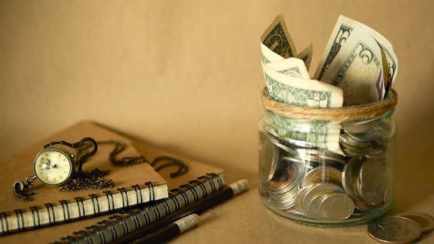 Knihy s penny sklenice plné mincí a bankovek. Školné nebo vzdělávací koncept financování. Stipendium peníze.