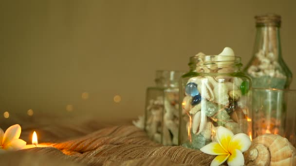 Glass bottle filled with seashells, corals, marine items with candle lights, plumeria frangipani flowers for decor