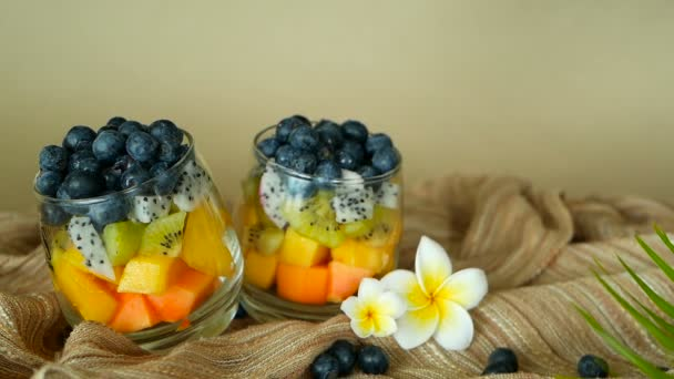 Colorful tropical mix salad in jar. Fresh various kind of raw organic berry and fruit in glass bowl. Healthy vegetarian eating, balanced, vegan diet. Rustic food background with falling blueberrys