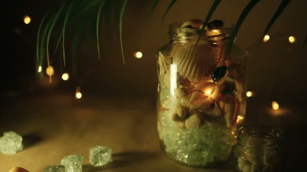 Glass jar of tropical shells for home decor. Marine style home accessories for beach themed interior decorating. Bottle filled with seashells, corals, marine items with lights in unfocused background.