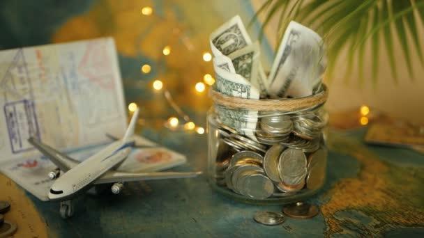Utazási költségvetés koncepció. Megtakarított pénzt a vakáció a világtérképen, útlevél- és sík üvegedénybe. Bankjegyek és érmék kaland. Megtakarítások, utazás. Gyűjt pénzt, utazás. Persely készpénz.