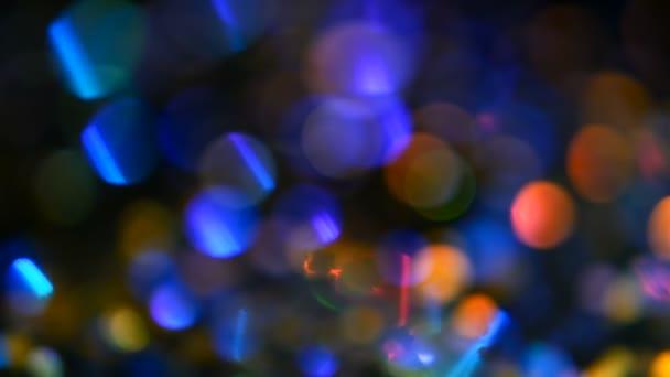 Defocused csillogó glitter tarka konfetti, fekete háttér. Holiday absztrakt ünnepi bokeh világos foltok.