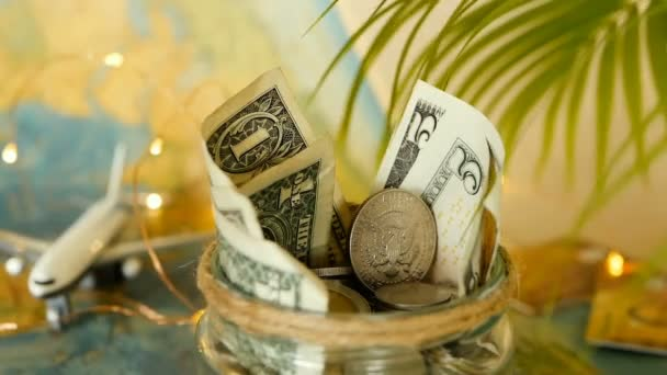 Concetto di bilancio di viaggio. Denaro risparmiato per vacanze in vaso di vetro sul fondo della mappa di mondo