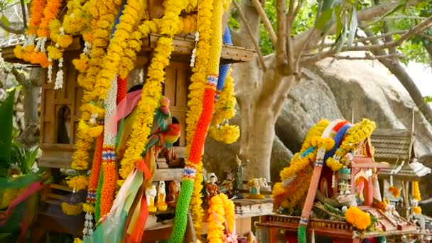 Wooden miniature guardian spirit house. Small buddhist temple shrine, colorful flower garlands. San phra phum.