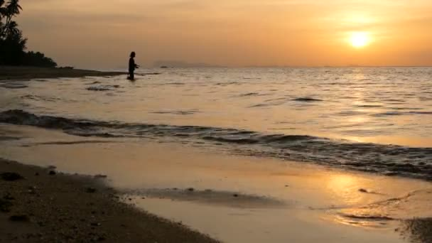 Fisherman silhouette in action when spinning on sunset time. Traditional Asian occupation and way of obtaining food