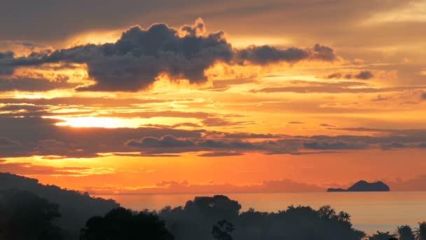 Timelapse tramonto di maestoso estate tropicale arancione sopra il mare con siluette delle montagne. Vista aerea del cielo nuvoloso drammatico crepuscolo, dorato sulle isole nelloceano. Fondo naturale oscurità vivido di vista sul mare