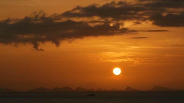 Majestátní tropické oranžové letní timelapse západ slunce nad mořem s hory siluety. Letecký pohled na dramatické soumraku, zlatý zamračená obloha nad ostrovy v oceánu. Živé soumraku krajina přírodní pozadí