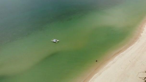 Letecká dron pohled na zelené oceánu s malou lodí a bílého písečného pobřeží s tropickými rostlinami v Thajsku. Cocunut dlaně na exotické pláži