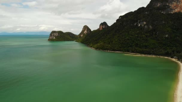 Drone view to paradise exotic coast and karst hill covered with green jungle forest in Thailand. Colorful ocean or sea