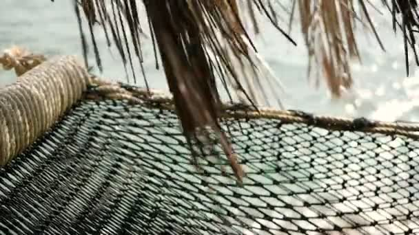 Close up of romantic cozy empty hammock with tropical ocean on the background. Vacation to paradise, travel to the sea, holiday in exotic beach resort, idyllic relaxation lazy time concept