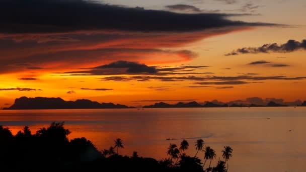 Tramonto di tempo reale maestosa estate tropicale arancione sopra il mare con siluette delle montagne. Vista aerea del cielo nuvoloso drammatico crepuscolo, dorato sulle isole nelloceano. Fondo naturale oscurità vivido di vista sul mare