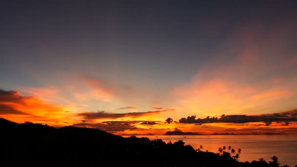 Majestic tropical orange summer timelapse sunset over sea with mountains silhouettes. Aerial view of dramatic twilight, golden cloudy sky over islands in ocean. Vivid dusk seascape natural background