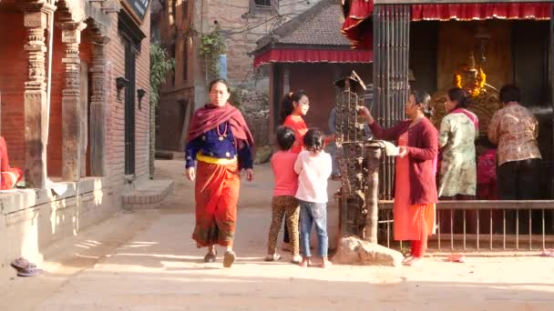 BHAKTAPUR, KATHMANDU, NEPAL - 18 October 2018 Newar people visiting hindu temple for worshiping in traditional clothes. Religious daily life of citizen, oriental ancient city after earthquake