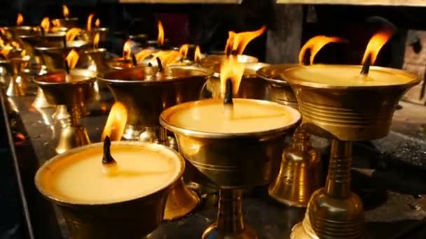 Hořící svíčky v chrámu. Pohled na zlaté lesklé misky s hořící plamen svíčky olej pro uctívání.