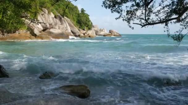Zöld szikla gyönyörű tenger közelében. Hullámzó durva zöld szikla a Ko Phangan-sziget közelében, napsütéses napon Thaiföld fenséges kék tenger. Egzotikus trópusi Paradise Beach.