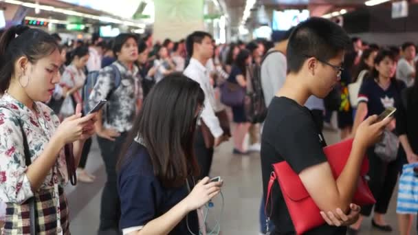 BANGKOK, THAILAND - 18 DECEMBER, 2018: Passenger at BTS Skytrain station in Bangkok Thailand, everybody looking down at smartphone while waiting for the BTS skytrain