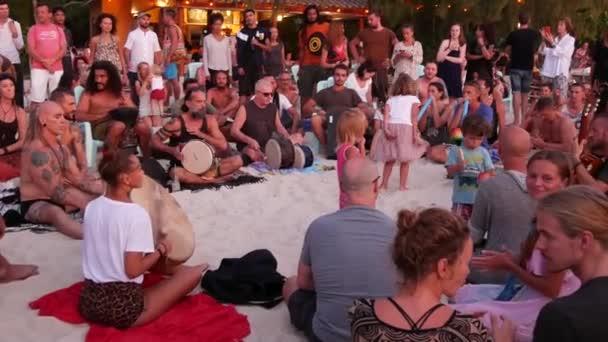 Phangan, Thailand - 23. Februar 2019 Zen Beach. Glückliche Menschen spielen Gitarre und Schlagzeug auf tropisches Paradies Sommer Küste bei Sonnenuntergang von vielen Menschen umgeben. Musikalischen Marmelade, Freiheit-Konzept, soziale Freizeit