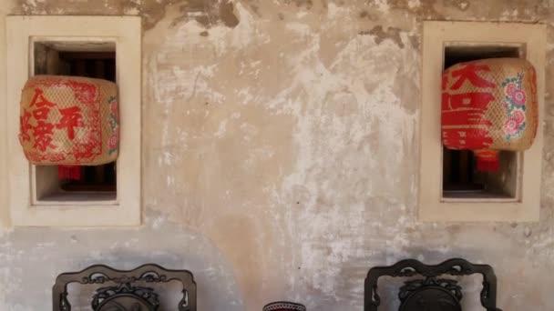 Keleti díszek közelében kopott betonfal. Különböző kínai díszek közelében szutykos betonfal keleti szobában.