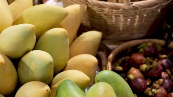 Ovoce a zelenina na venkovském stánku. Různé čerstvé zralé ovoce a zelenina uvedené na rustikální orientální stánek na trhu. Zelené a žluté mango a mangostany v košíku.