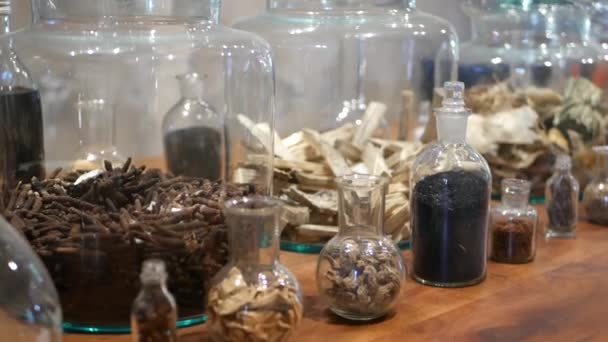 Sklenice se sušenými bylinkami v lékárna. Skleněné skleničky a lahve s rozmaněnými bylinkami na poličce v retroorientální lékárně