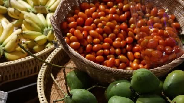 Ovoce a zelenina v rustikálním stánku. Různé čerstvé zralé ovoce a zelenina umístěné na venkovském orientálním stánku na trhu. Zelené mango, rajčata a žlutý banán.