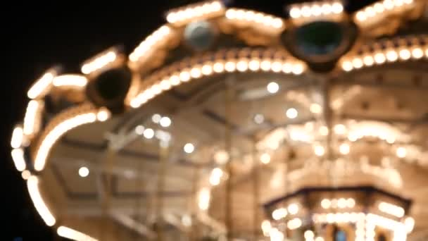 Illuminated blurred merry go round in park. Brightly illuminated roundabout spinning in wonderful amusement park at night