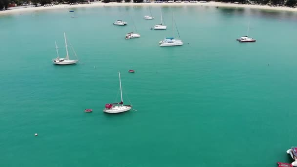 Yachts floating in calm bay. Many luxury sailboats floating on tranquil water in bay of turquoise sea. Koh Samui paradise island in oriental Thailand