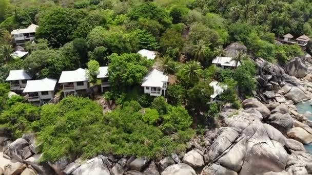 Kis házak a trópusi szigeten. Apró hangulatos bungalók partján Koh Samui sziget közelében nyugodt tenger napsütéses napon Thaiföldön. Vulkáni sziklák és sziklák drone felülnézetben.