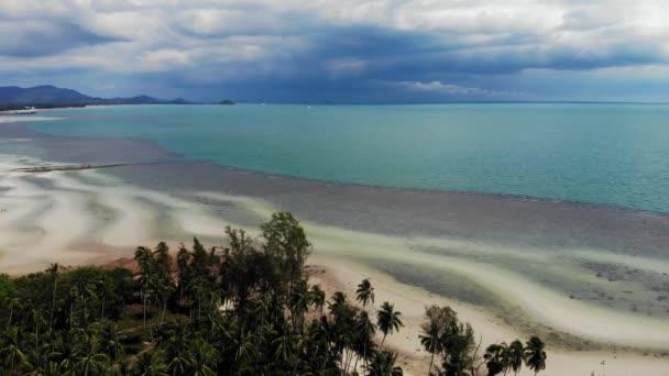 Szokatlan part fehér homok. Lélegzetelállító táj homokos hullámzó tengerparton. Ázsia paradicsomi szigetei. Drone kilátás, természetes idilli jelenet, kókusz pálmák a tengerparton. Vihar a trópusokon.