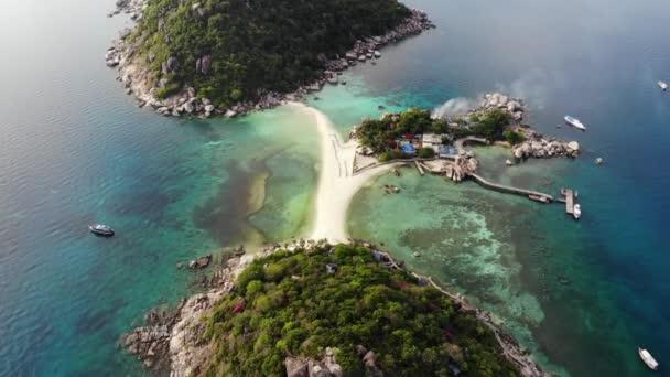 Nyugodt színes azúrkék türkiz tenger közelében apró trópusi vulkáni sziget Koh Tao, egyedülálló kis paradicsom Nang Yuan. Drone kilátás nyugodt víz közelében köves parton és a zöld dzsungelben a napsütéses napon Thaiföldön.