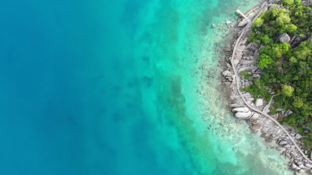 Calm colorful azure turquoise sea near tiny tropical volcanic island Koh Tao, unique small paradise Nang Yuan. Drone view of peaceful water near stony shore and green jungle on sunny day in Thailand.